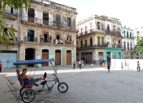 A bicycle taxi driver rests while waiting for a customer in Old Havana, Cuba